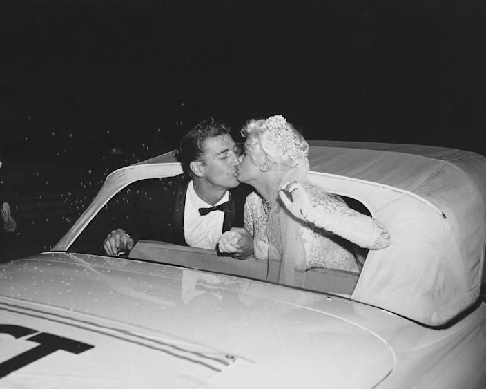 <p>Jayne Mansfield and Mickey Hargitay share one last newlywed kiss in front of their wedding guests as they leave their reception in Los Angeles. </p>