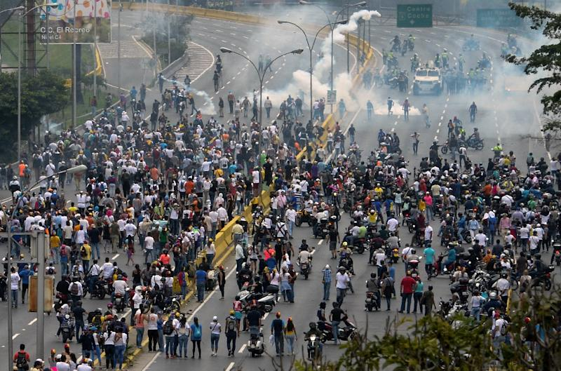 Police fired tear gas and rubber bullets to break up thousands of marchers as they reached a vital freeway in Caracas