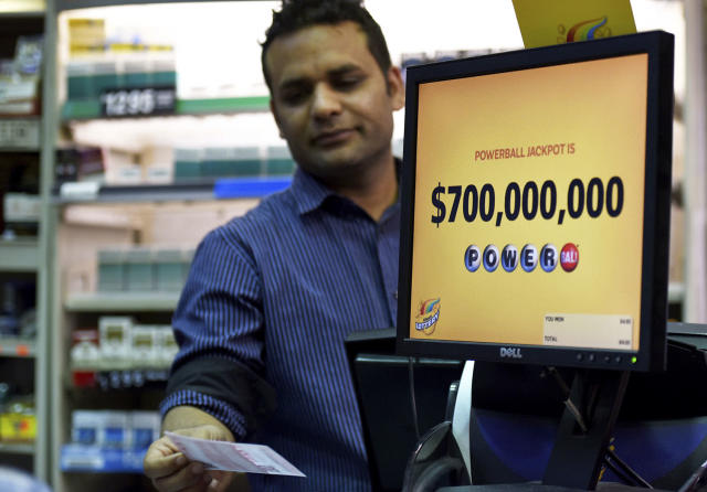 <p>Screen display the lottery prizes, as store clark Malik Imran serves customer, Aug. 22, 2017, in Chicago. Officials estimated jackpot for Wednesday night's Powerball lottery game has climbed to $700 million, making it the second largest in U.S. history. (Photo: G-Jun Yam/AP) </p>