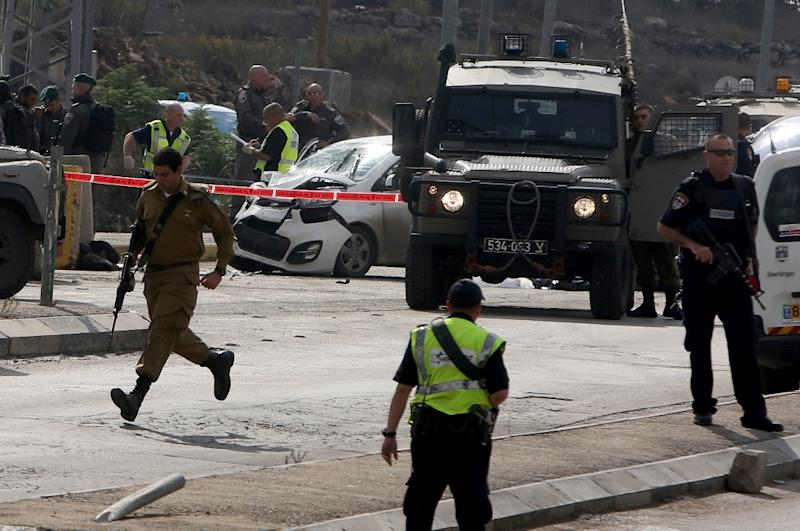 Israeli security forces gather at the scene where a Palestinian man was shot dead by Israeli security forces after ramming his car into a group of Israelis at Tapuah junction, south of Nablus in the West Bank, on November 8, 2015 (AFP Photo/Jaafar Ashtiyeh)