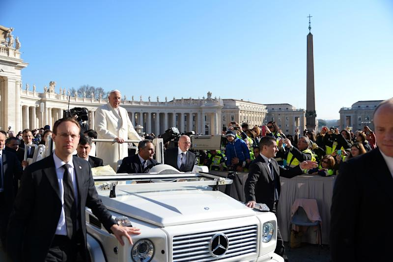 Pope Francis stands on the popemobile surrounded by security staff during his weekly general audience at St Peter's square on February 18, 2015 at the Vatican (AFP Photo/Vincenzo Pinto)
