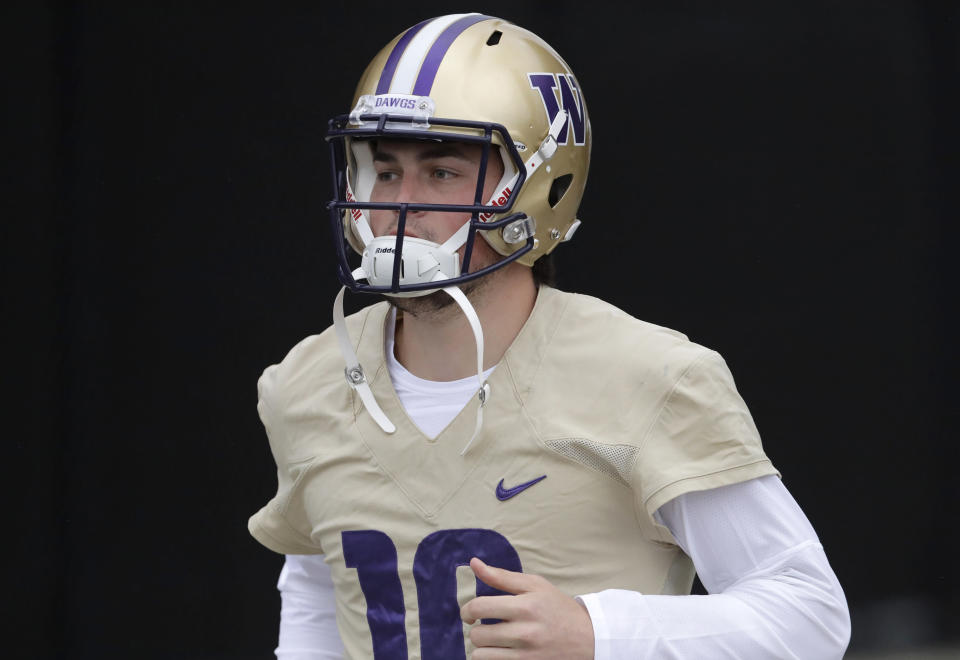 FILE - In this April 3, 2019, file photo, Washington quarterback Jacob Eason jogs to the field for NCAA college football practice in Seattle. Eason replaces Jake Browning, who threw for 3,192 yards with 16 touchdowns last season, leading the Huskies to a 10-4 record and the Pac-12 championship. Browning now plays for the NFLs Minnesota Vikings.(AP Photo/Ted S. Warren, File)