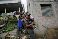 Honduran migrants walk between houses in Agua Caliente hoping to cross into Guatemala and join a caravan trying to reach the U.S, in Honduras October 17, 2018. REUTERS/Jorge Cabrera