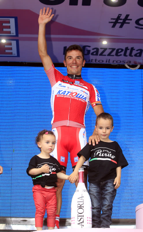 Spanish rider Joaquim Rodriguez poses with his children on the podium after taking second place of the Tour of Italy (Giro d'Italia) in Milan on May 27, 2012. AFP PHOTO / LUK BENIESLUK BENIES/AFP/GettyImages