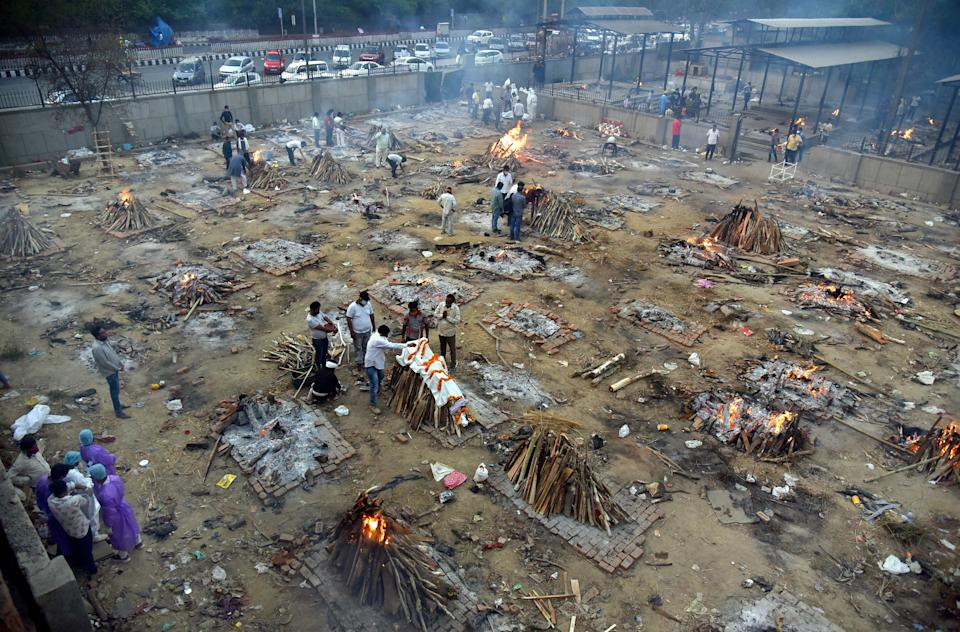 <p>A mass funeral takes place for Covid-19 victims at a cremation ground in New Delhi, India on 27 April 2021</p> (EPA)