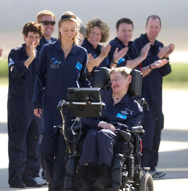 <p>Astrophysicist Stephen Hawking is assisted off the tarmac at the Kennedy Space Center by his caregiver, Monica Guy, as he is applauded by members of the flight crew after completing a zero-gravity flight, Thursday, April 26, 2007, in Cape Canaveral, Fla. (Photo: Peter Cosgrove/AP) </p>