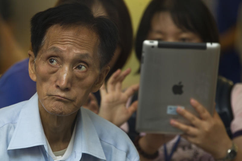 FILE - In this Friday, July 20, 2012 file photo, an elderly man, left, watches tutorial videos after he bought a new iPad at an Apple Store in Beijing. Apple apologized to Chinese consumers after government media attacked its repair policies for two weeks in a campaign that reeked of economic nationalism. (AP Photo/Alexander F. Yuan)