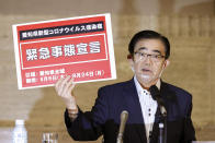 """Aichi Gov. Hideaki Ohmura shows off a placard """"State of Emergency"""" in Nagoya, Aichi prefecture, central Japan, Thursday, Aug. 6, 2020. Ohmura announced a state of emergency Thursday due to rising virus cases and asked businesses and people to curb their activities, especially during an upcoming holiday. Aichi prefecture has been seeing more than 100 new infections reported daily since mid-July after an extended period of zero new daily cases. (Kyodo News via AP)"""