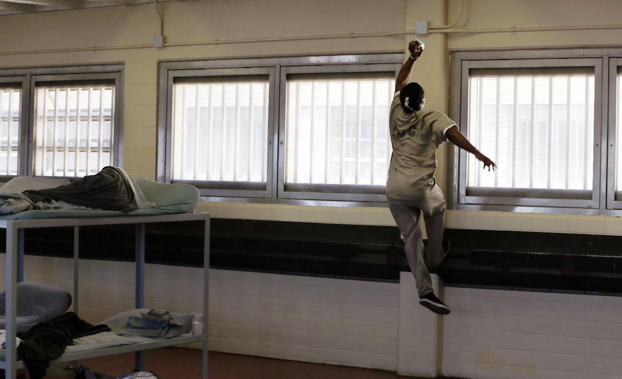 In this June 26, 2014 photo, an inmate, Nick, uses a small milk carton as a basketball and leaps up for a dunk at the Cook County Jail's Division 2, Dorm 2 building in Chicago. Unlike prisons where inmates served extended sentences, jails hold those trying to make bail while awaiting trial, or serving shorter terms. Dorm 2 has 464 bunks, most of them reserved for inmates with mental illnesses. They're always full. (AP Photo/Charles Rex Arbogast)