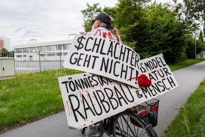 """04 July 2020, North Rhine-Westphalia, Rheda-Wiedenbrück: An activist from the """"Alliance Together Against the Animal Industry"""" stands with his bicycle and two banners with the inscription: """"$chlachter geht nicht"""" and Tönnies (k)ein Geschäftsmodell - Raubbau an Natur & Mensch"""" in front of the Tönnies company complex. Photo: Guido Kirchner/dpa (Photo by Guido Kirchner/picture alliance via Getty Images)"""
