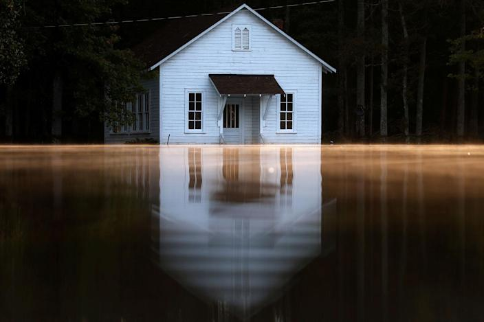 <p>OCT. 11, 2016 — Mist rises off the water as a flooded building is pictured after Hurricane Matthew passes in Lumberton, North Carolina. (Carlo Allegri/Reuters) </p>