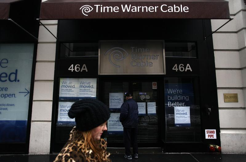 A woman walks past the old Time Warner Cable headquarters as a man tries to enter the building in New York