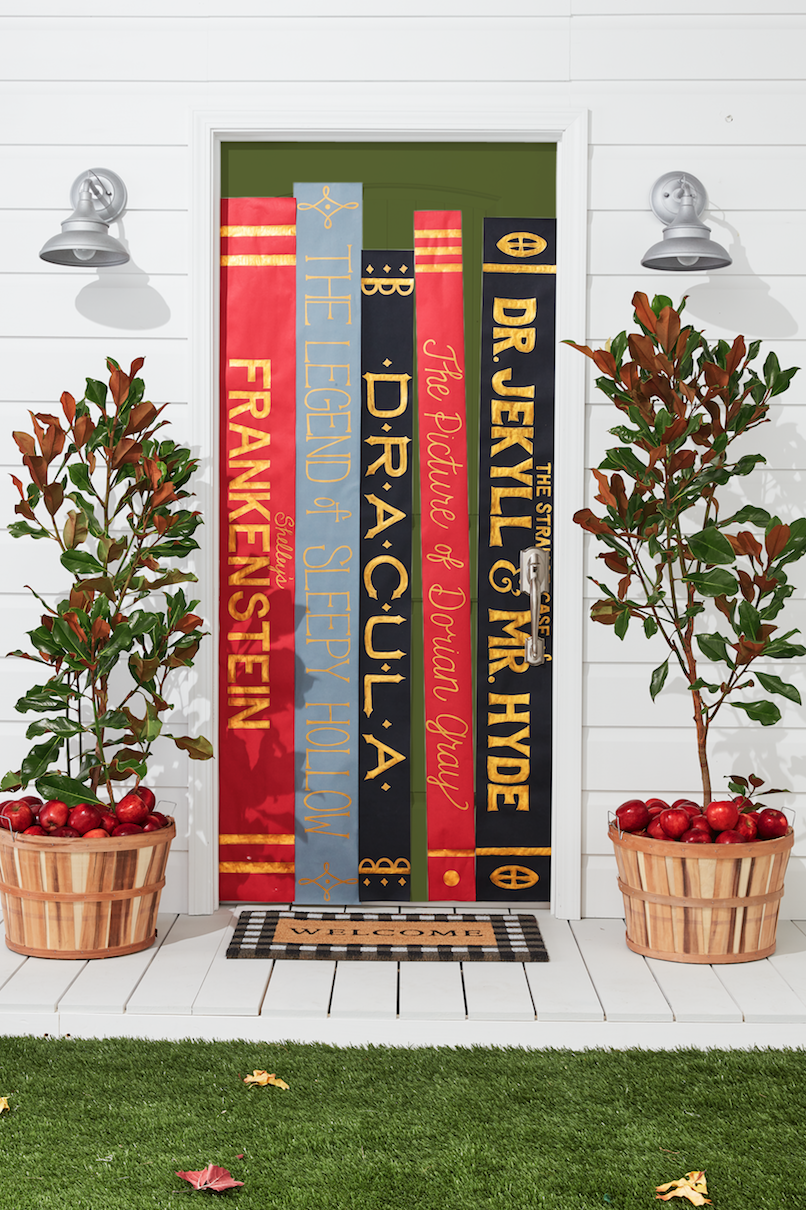 <p>Pay homage to your favorite creepy titles with a cool book-spine display. To make it, cut long, thin rectangular pieces of different colored kraft paper and draw titles of books on the paper. Outline the letters with gold paint pens and fill in the outline with a paint pen or gold acrylic paint. Attach the display to your door with double-sided tape. </p>