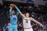 Denver Nuggets center Nikola Jokic, right, disrupts shot by Charlotte Hornets forward P.J. Washington during the first half of an NBA basketball game in Charlotte, N.C., Thursday, March 5, 2020. (AP Photo/Nell Redmond)