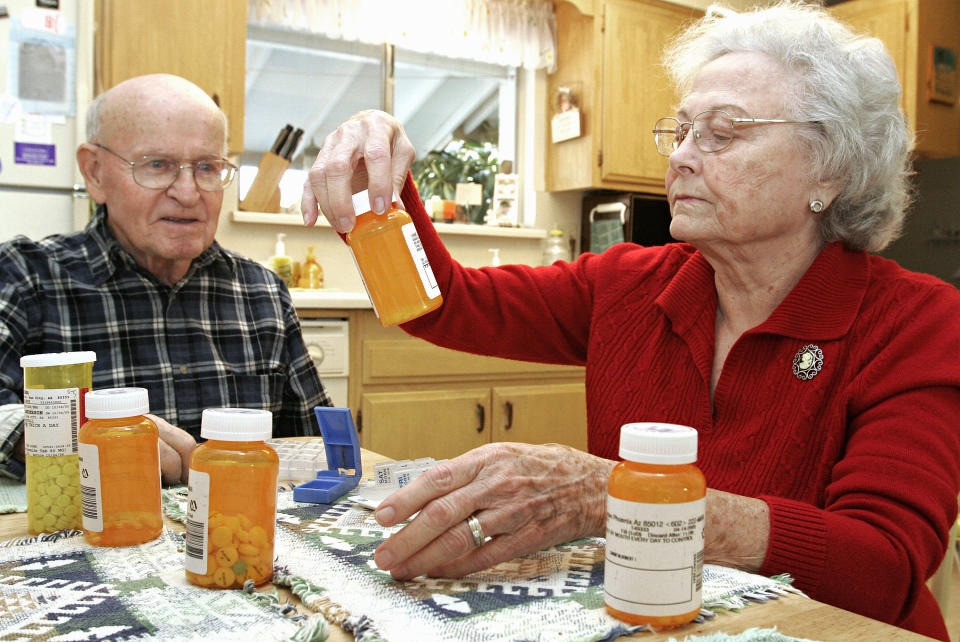 Toby Anderson watches as his wife Amy divides his five prescription drugs into a weekly schedule. (Photo: Jeff Topping/Getty Images)
