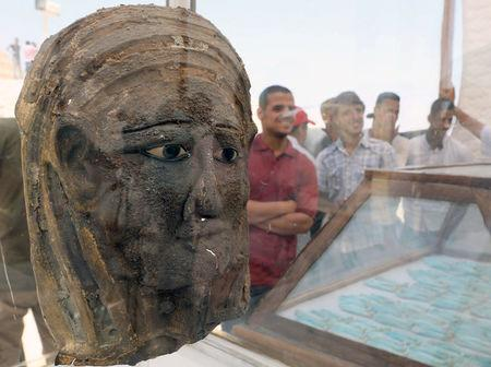 A silver mask gilded with gold seen inside a glass casing at the site of a recently discovered burial shaft near Egypt's Saqqara necropolis, in Giza