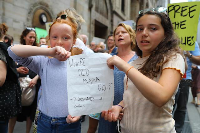 Charlotte and Amelia of Brooklyn chant slogans and share a sign in a rally against President Trump's immigration policy in New York City on June 20, 2018. (Photo: Gordon Donovan/Yahoo News)