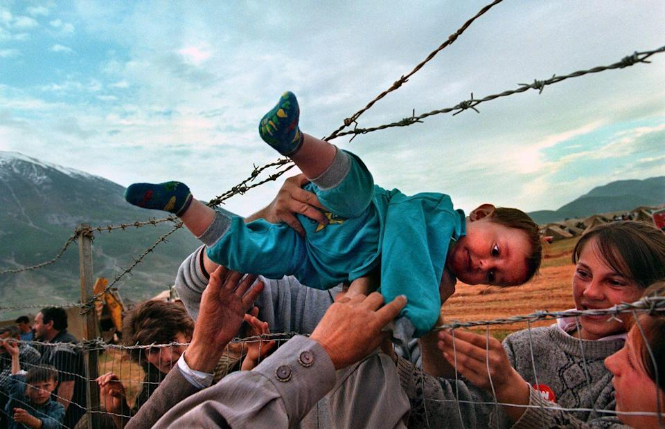 <p>1999. Getty Caption: Kosovar refugee Agim Shala, 2 years old, is passed through the barbed wire fence into the hands of grandparents at the camp run by United Arab Emirates in Kukes, Albania.</p>