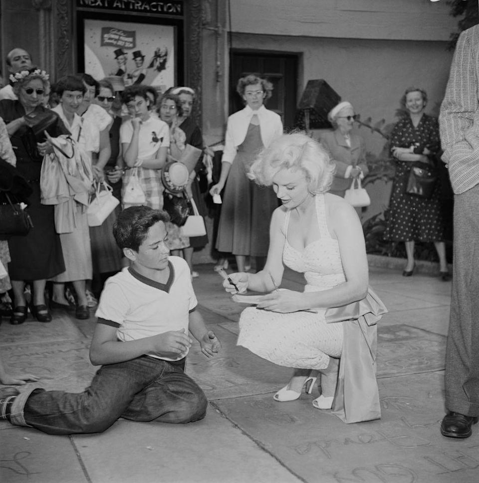 <p>Marilyn had fans of all ages. Here, she signs for a young boy at the Grauman's event. </p>