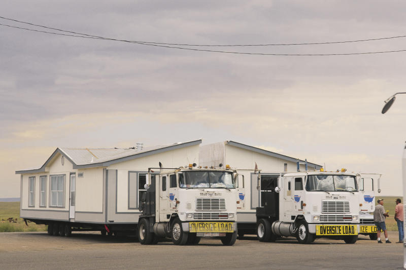 Picture of two trucks relocating a home, which was split down the middle for relocation.