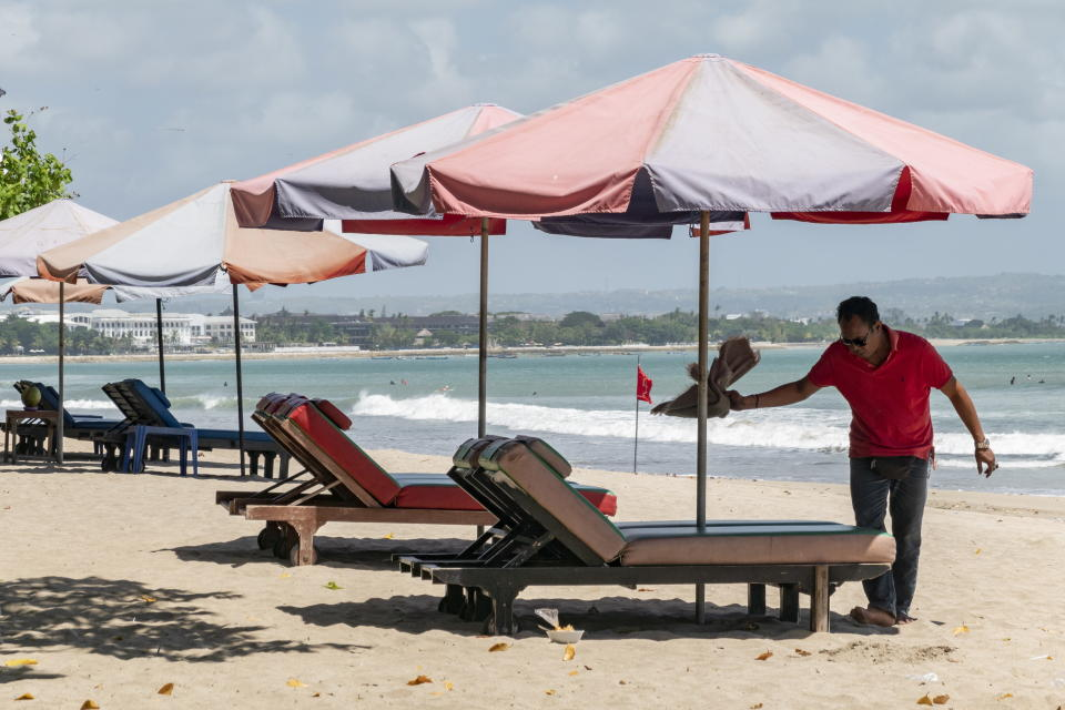 A man sets up sea-side loungers at a beach in Kuta, Bali. Source: AAP