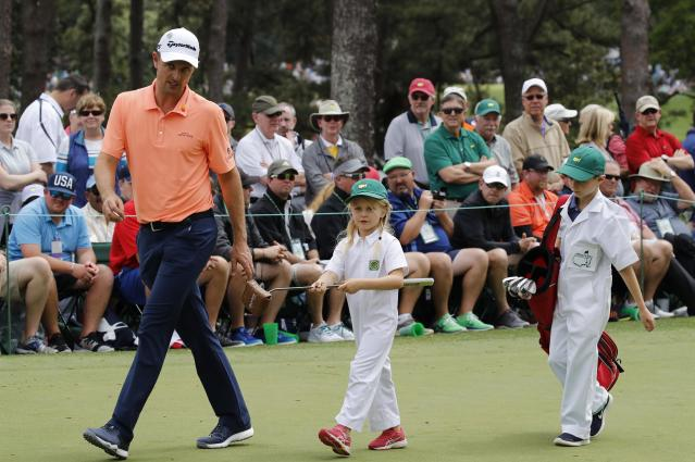 Justin Rose of England walks off the first green with his two children during the par 3 contest held on the final day of practice for the 2018 Masters golf tournament at Augusta National Golf Club in Augusta, Georgia, U.S. April 4, 2018. REUTERS/Mike Segar