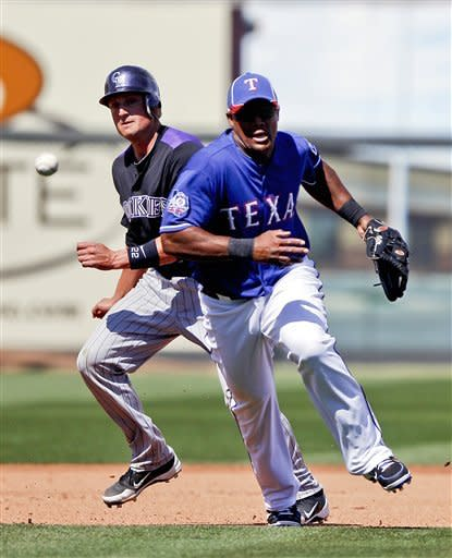 Texas Rangers third baseman Adrian Beltre, right, boots a slow grounder hit by Colorado Rockies' Brendan Harris as Jordan Pacheco heads for third base during the fourth inning of a spring training baseball game Wednesday, March 14, 2012 in Surprise, Ariz. (AP Photo/Lenny Ignelzi)