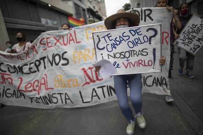 """Women from the feminist group """"Tinta Violeta"""" march during a protest marking International Women's Day and demanding justice for women who have been victims of violence in Caracas, Venezuela, Monday, March 8, 2021. (AP Photo/Ariana Cubillos)"""
