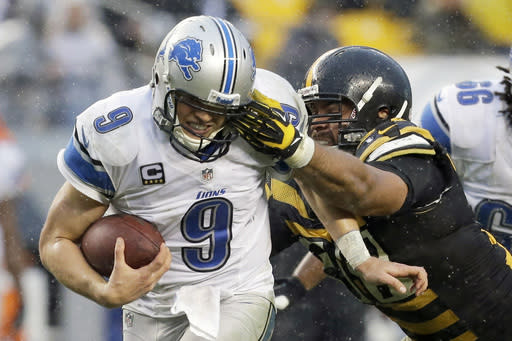 Detroit Lions quarterback Matthew Stafford (9) scrambles for a first down as Pittsburgh Steelers defensive end Cameron Heyward (97) defends in the second half of an NFL football game in Pittsburgh, Sunday, Nov. 17, 2013. (AP Photo/Gene J. Puskar)