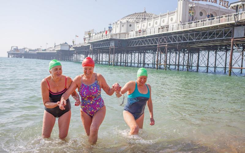 Lizzie Ward, Michelle Benny and Mary Wedges: Swimmers enjoy taking a dip next to Brighton pier - SWNS.com