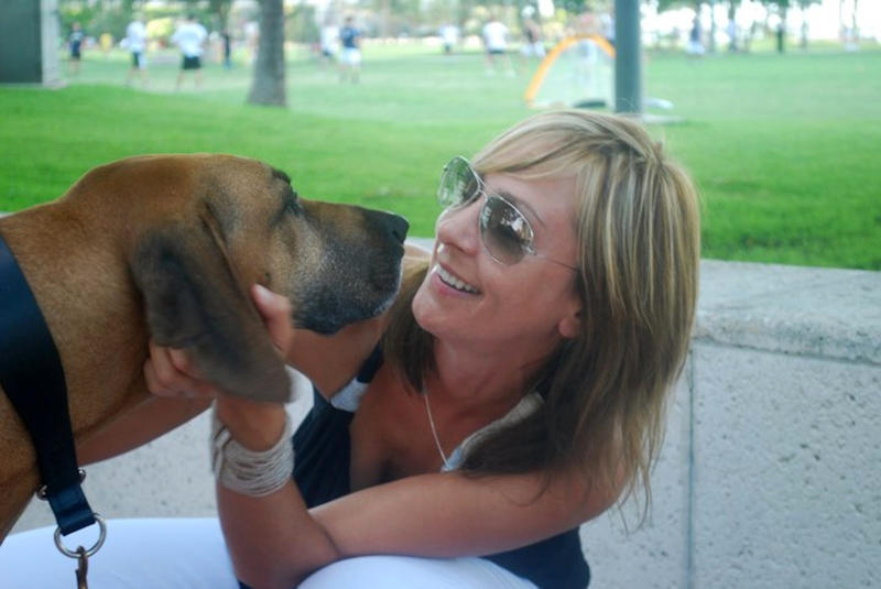 In this 2011 photo released by Sniff Pet Candles, Jenn Mohr, founder of Sniff Pet Candles, pets Rufus her 8-year-old Rhodesian ridgeback rescue dog in Miami, Fla. Mohr says she can't forgive Republican presidential hopeful Mitt Romney for making his dog ride on top of the car during a 1983 family trip to Canada. But many dog owners feel the whole doggone issue is a distraction. (AP Photo/Sniff Pet Candles)