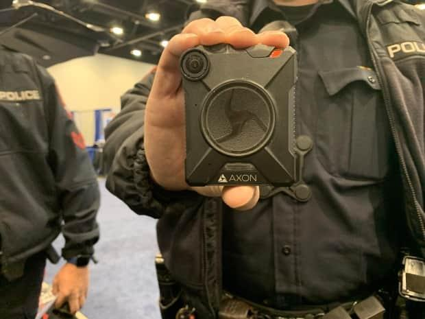 A Calgary police officer shows his body-worn camera. Only a handful of police forces in Canada use them, mainly in larger cities. (Helen Pike/CBC - image credit)