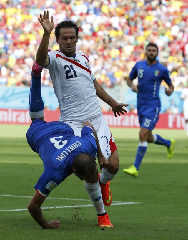 Italy's Giorgio Chiellini tumbles beside Costa Rica's Marco Urena during their 2014 World Cup Group D soccer match at the Pernambuco arena in Recife June 20, 2014. REUTERS/Yves Herman (BRAZIL - Tags: SOCCER SPORT WORLD CUP)