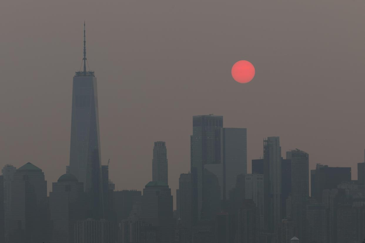 The sun, appearing orange due to smoke haze from forest fires, rises behind the skyline in New York City