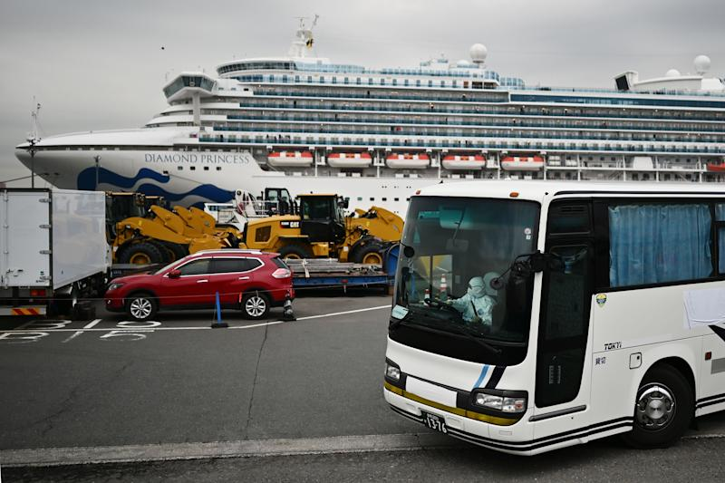 A bus with a driver wearing full protective gear departs from the dockside next to the Diamond Princess cruise ship.
