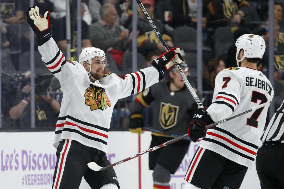 Chicago Blackhawks defenseman Calvin de Haan, left, celebrates after scoring against the Vegas Golden Knights during the second period of an NHL hockey game Wednesday, Nov. 13, 2019, in Las Vegas. (AP Photo/John Locher)