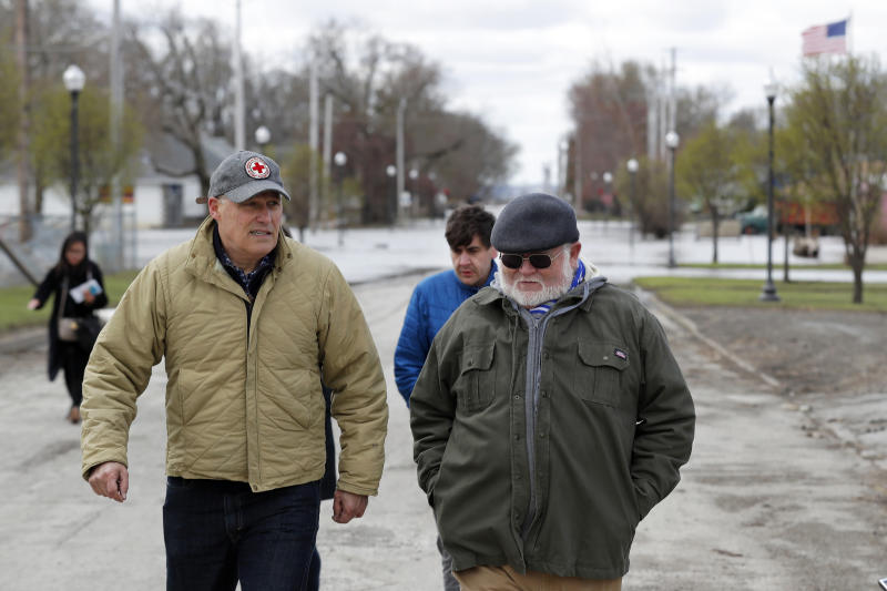 2020 Democratic presidential candidate Washington Gov. Jay Inslee, left, walks with climate analyst John Davis, of Hamburg, Iowa, while touring flood damage, Friday, April 12, 2019, in Hamburg, Iowa. (AP Photo/Charlie Neibergall)
