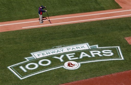 A member of the Fenway Park grounds crew prepares the first base line before a baseball game between the Boston Red Sox and the Tampa Bay Rays in Boston, Friday, April 13, 2012. The Red Sox will celebrate the 100th anniversary of Fenway's opening when they host the New York Yankees next Friday. (AP Photo/Michael Dwyer)