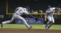 Los Angeles Dodgers first baseman Joc Pederson (31) makes an error on a grounder hit by Arizona Diamondbacks' David Peralta as Dodgers second baseman Enrique Hernandez, right, moves in to help out during the first inning of a baseball game Wednesday, June 26, 2019, in Phoenix. (AP Photo/Ross D. Franklin)