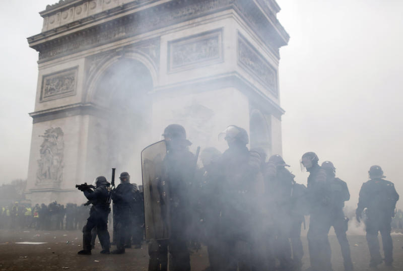 FILE - In this Saturday, Jan. 12, 2019 file photo riot police take position around the Arc de Triomphe during clashes with yellow vest protesters, in Paris, France. (AP Photo/Thibault Camus, File)