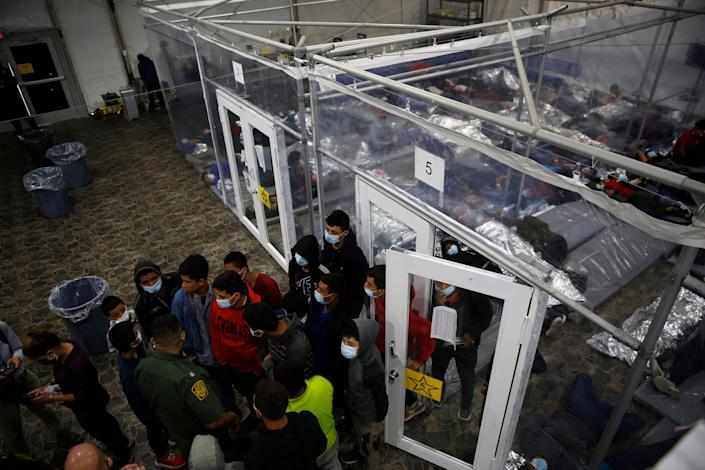 Minors talk to an agent outside a pod at the Department of Homeland Security holding facility run by the Customs and Border Patrol (CBP) on March 30, 2021 in Donna, Texas. The Donna location is the main detention center for unaccompanied children coming across the U.S. border in the Rio Grande Valley. The children are housed by the hundreds in eight pods that are about 3,200 square feet in size. Many of the pods had more than 500 children in them. The youngest of the unaccompanied minors are kept separate from the rest of the detainees. The Biden administration has just allowed journalists inside its main detention facility at the border for migrant children. It is an overcrowded tent structure where more than 4,000 kids and families are kept in pods, with the youngest kept in a large play pen with mats on the floor for sleeping. (Photo by Dario Lopez-Mills - Pool/Getty Images)