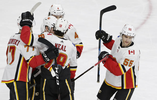 Calgary Flames' Noah Hanifin (55) celebrates with teammates following his goal against the Carolina Hurricanes during the third period of an NHL hockey game in Raleigh, N.C., Sunday, Feb. 3, 2019. (AP Photo/Gerry Broome)