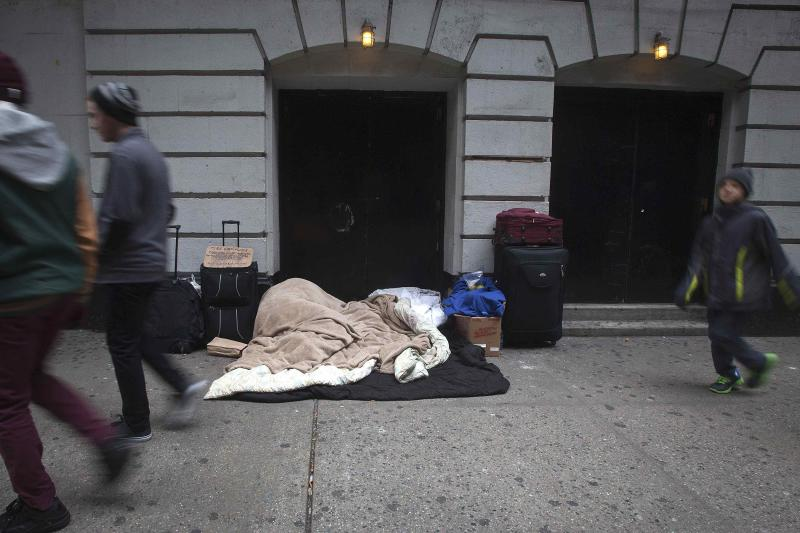 Homeless person sleeps as people walk past near Times Square on Black Friday in New York