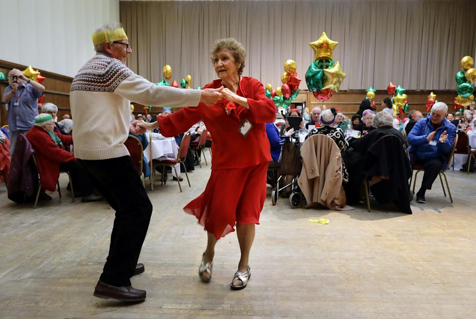Anita Monk and her neighbour John Everett dance during a Christmas Dinner event for older people at Hammersmith and Fulham Town Hall in London, Britain December 25, 2016. REUTERS/Kevin Coombs