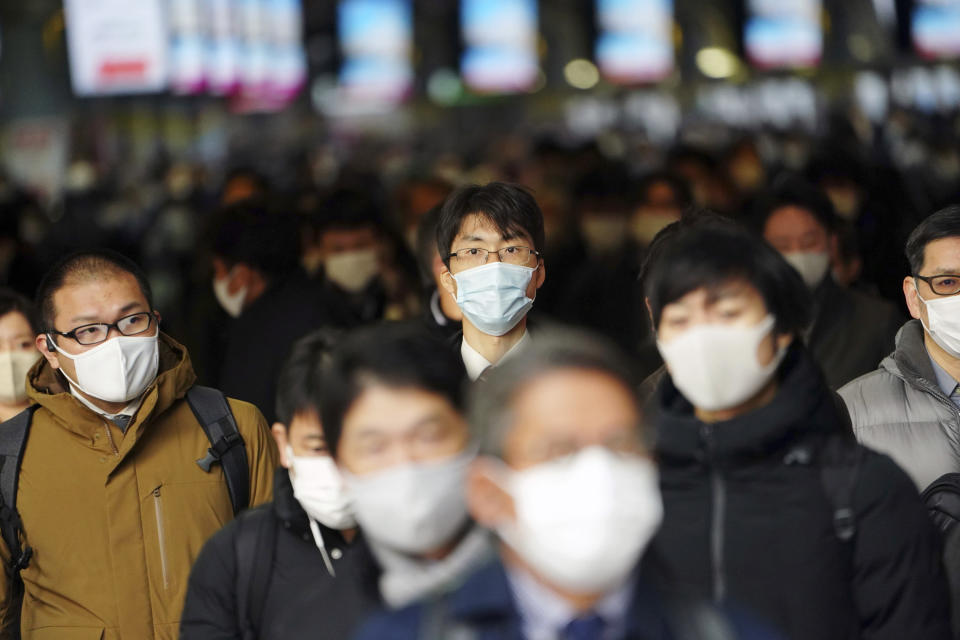 FILE - In this Jan. 4, 2021, file photo, people commute on the first business day of the year at a train station in Tokyo. Opposition to the Tokyo Olympics is growing with calls for a cancellation as virus cases rise in Japan. The International Olympic Committee and local organizers have already said another postponement is impossible, leaving cancellation, or going ahead, as the only options. (AP Photo/Eugene Hoshiko, File)