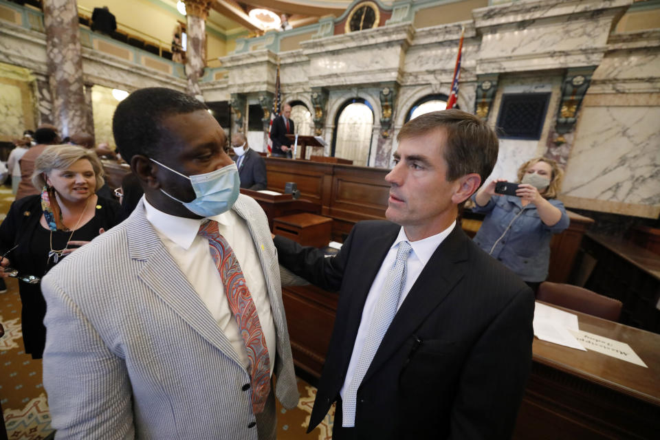 Sen. Briggs Hopson, R-Vicksburg, right, confers with Sen. Juan Barnett, D-Heidelberg, after the Senate voted to change the Mississippi state flag Sunday, June 28, 2020, at the Capitol in Jackson, Miss. Hopson presented the bill to the body. Both chambers of the Mississippi Legislature passed the bill to take down the state flag, which contains the Confederate battle emblem. Gov. Tate Reeves has already said he would sign whatever flag bill the Legislature decides on. (AP Photo/Rogelio V. Solis)