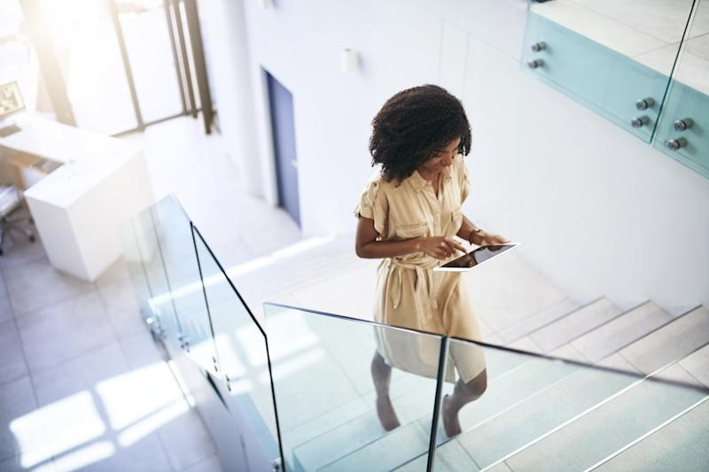 Shot of a young businesswoman using a digital tablet while walking up a staircase in an office