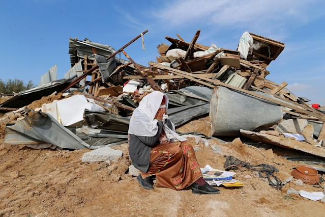 <p>JAN. 18, 2017 – An Arab Israeli woman sits next to ruins from her dwellings which were demolished by Israeli bulldozers in Umm Al-Hiran, a Bedouin village in Israel's southern Negev Desert. The Israeli army says it is simply carrying out court rulings against unauthorized building by Palestinians in Area C. Foreign diplomats and rights groups see it as part of a broader move to seize land for potential Jewish settlement expansion. (Photo: Ammar Awad/Reuters) </p>