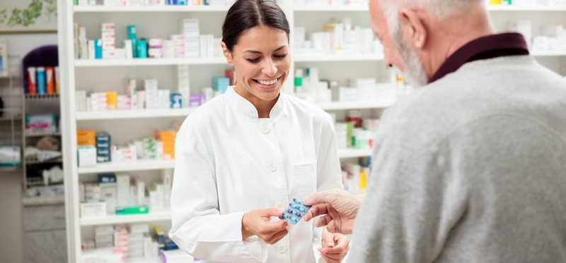 Pharmacist handing medication to an older male.