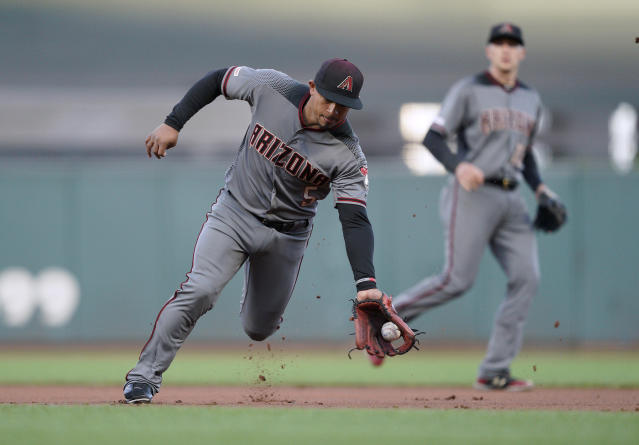 Arizona Diamondbacks second baseman Eduardo Escobar reaches out to field a grounder hit by San Francisco Giants' Mike Yastrzemski before throwing him out at first base during the first inning of a baseball game in San Francisco, Tuesday, Aug. 27, 2019. (AP Photo/Tony Avelar)